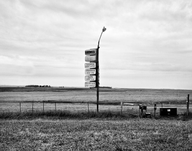 Black and white landscape photograph of Minnesota prairie in early Spring, with a vintage sign in the center of the frame.