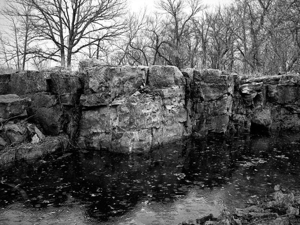Black and white landscape photograph of the red stone quarry pit at Pipestone, Minnesota, filled with rainwater and winter meltwater. The quarry at Pipestone has been used by Native Americans for 3,000 years to mine stone to make ceremonial tobacco pipes. The site is still used for this purpose today, and is considered sacred by the tribes who use it.
