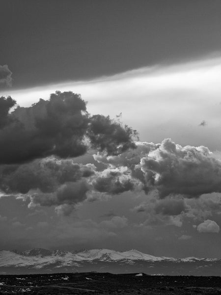 Black and white landscape photograph of turbulent storm clouds over the snowy mountains of Eastern Wyoming.