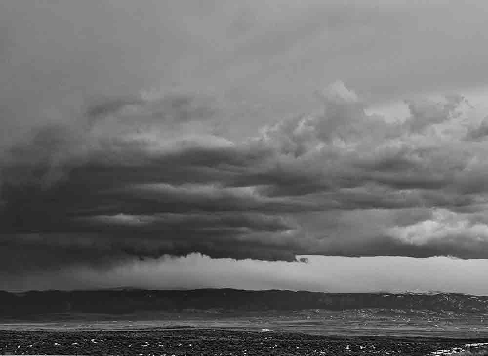 Black and white landscape photograph of dark, heavy storm clouds passing over Sheridan, Wyoming.