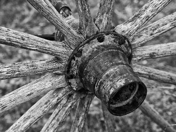 Black and white photograph of a weathered antique wagon wheel on an abandoned buckboard wagon in the wilderness of Wyoming.