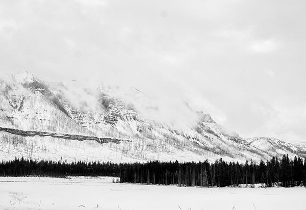 Black and white winter landscape photograph of cloudy Wyoming mountains in snow.