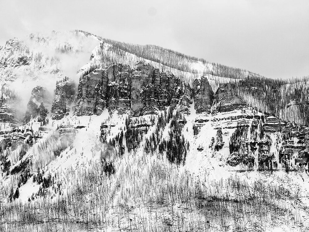 Black and white landscape photograph of Wyoming mountains in snow.