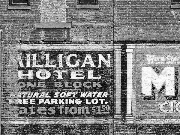 Black and white fine art photograph of a painted ad for the Milligan Hotel on a brick wall in Miles City Montana.