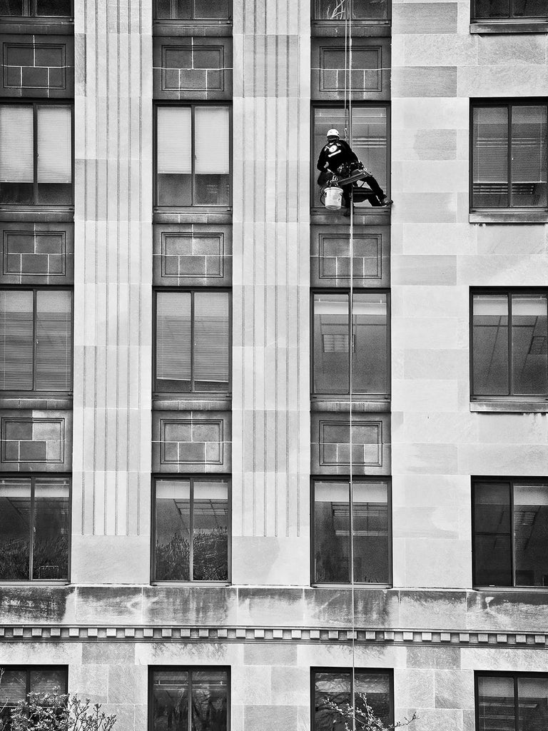 Black and white photograph of a guy washing office windows outside a high-rise building on the Capitol Square in downtown Madison, Wisconsin.