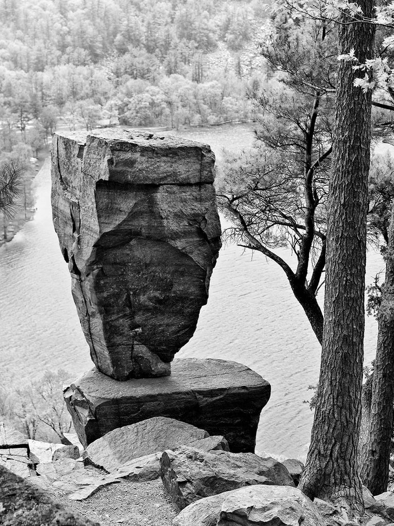 Black and white landscape photograph of the famous Balanced Rock overlooking Devil's Lake in Wisconsin. Devil's Lake was formed naturally by the action of glaciers during the last ice age.