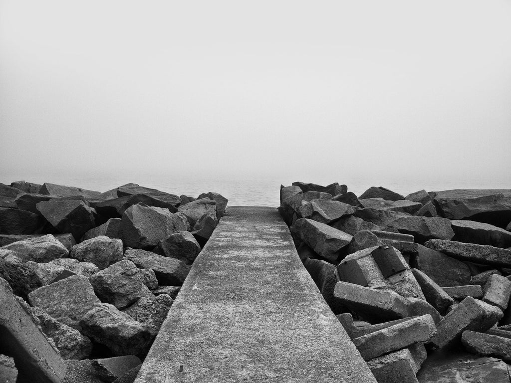 Black and white landscape photograph of a sidewalk that seems to end at nothingness, with just a little bit of Lake Michigan visible in dense fog.
