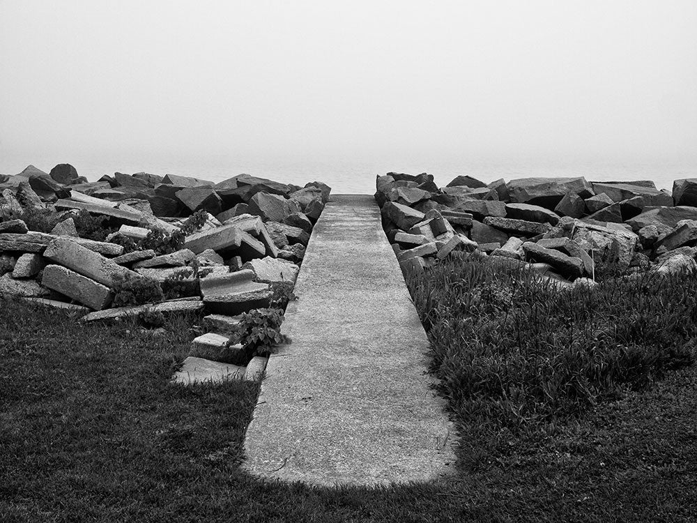 Black and white landscape photograph of a sidewalk leading to nowhere, but it actually goes to the shore of Lake Michigan, which is hidden in a thick blanket of early morning fog.