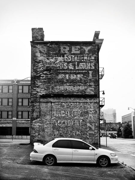 Black and white photograph of a narrow old building in Racine, Wisconsin, featuring layers of fading wall ads on its brick exterior wall.