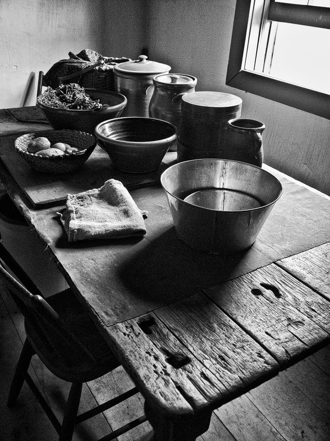 Black and white photograph of a rough and rustic kitchen table covered with jars and bowls, found in an old farmhouse. Imagine the stories this old table could tell.
