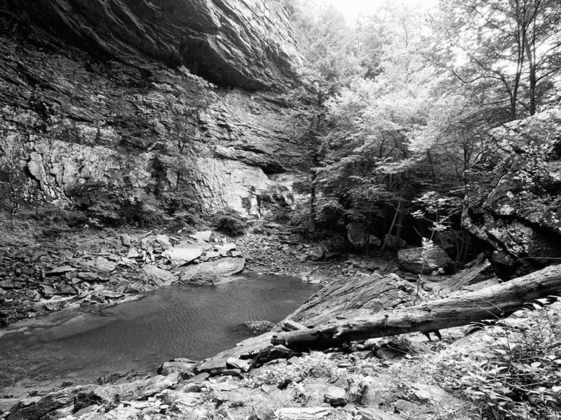 Black and white landscape photograph of the rocky pool at the base of Ozone Falls, Tennessee. The pool is fed by Fall Creek, which falls 110' from the cliff above, and flows out through a subterranean passage and back above ground further downstream.