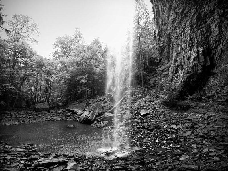 Black and white landscape photograph the tall waterfall dropping into a rocky pool at Ozone Falls, Tennessee.