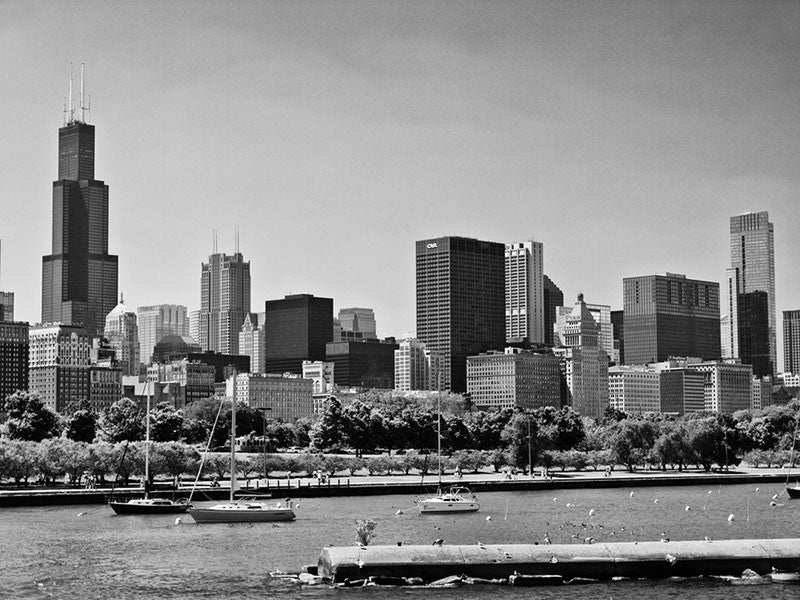 Black and white photograph of the Chicago skyline with sailboats in the foreground.