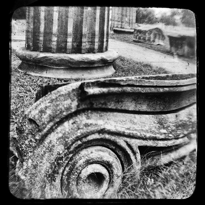 Black and white through-the-viewfinder photograph of an antique Ionic column fragments in Nashville. Through-the-viewfinder (TTV) photography is an alternative style of photography where a camera is focused though the view finder of another camera -- usually a vintage or antique model. This technique gives a uniquely distorted quality.
