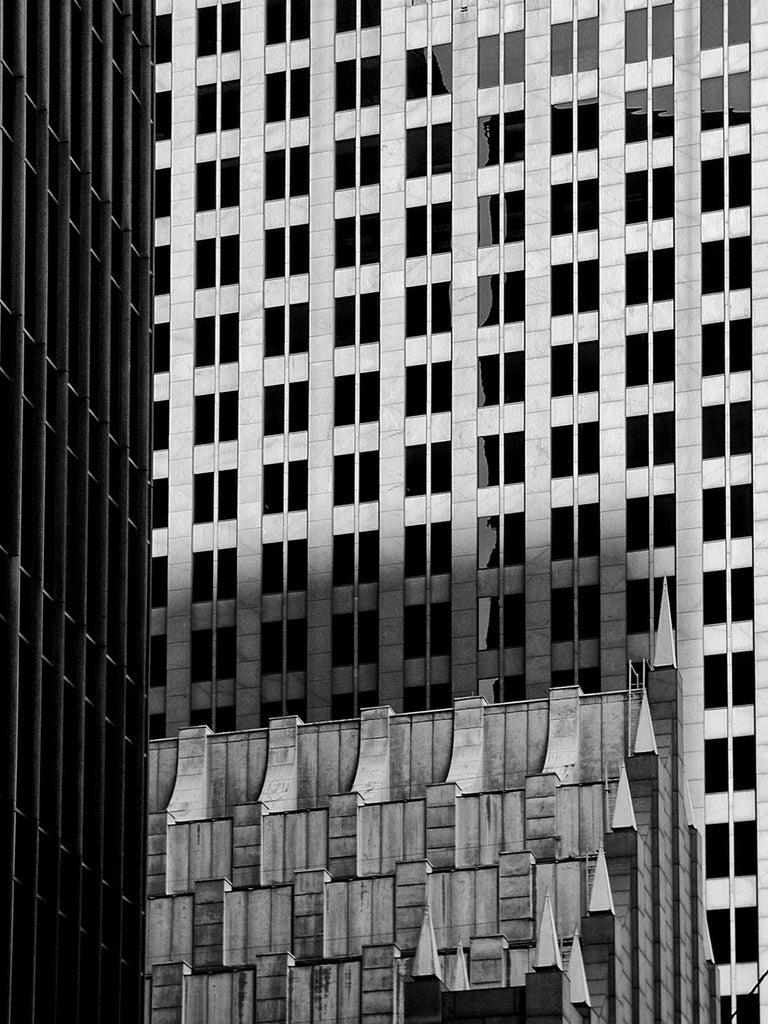 Black and white architectural photograph of the overlapping lines and grids of downtown Houston skyscrapers.