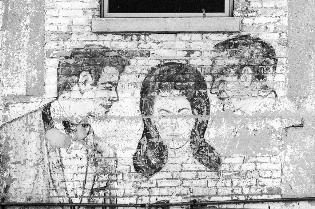 Black and white photograph of an old, fading, and peeling fashion ad on a brick wall in downtown Milwaukee, showing a painting of people in 60s-style evening wear.
