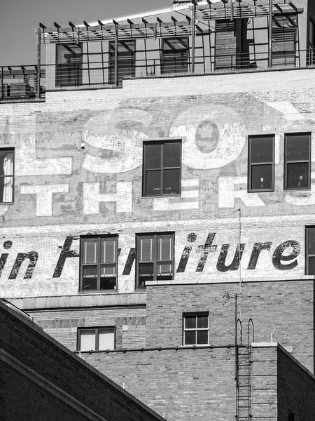 Black and white architectural photograph of buildings in downtown Milwaukee featuring faded vintage advertising signs cut through with modern windows added later