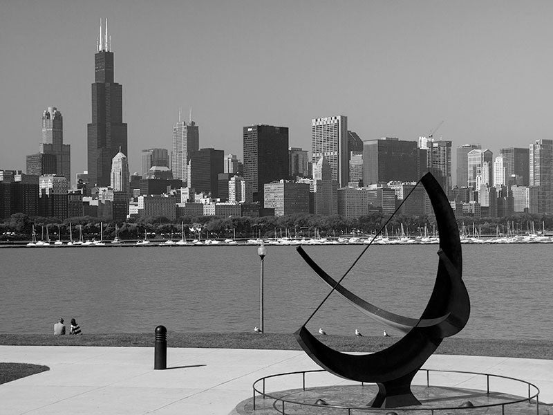 "Black and white photograph of the great Chicago skyline, as seen from the Adler Planetarium location on the lakeshore of Lake Michigan. In the foreground is ""Man Enters the Cosmos"" sculpture by Henry Moore."