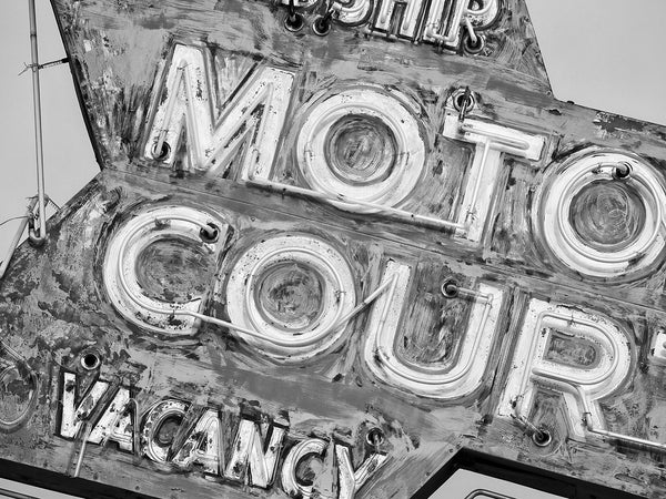 Black and white detail photograph of a beautifully faded vintage motel neon sign. The fading colors have left a very painterly effect.