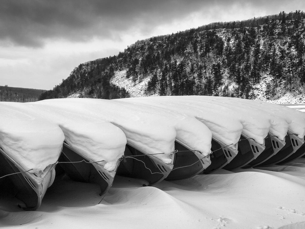 Black and white landscape photograph of row boats stored for winter, covered in a blanket of snow at Devil's Lake in Wisconsin. Devil's Lake was formed naturally by the action of glaciers during the last ice age.
