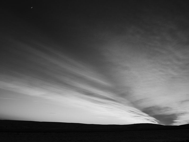 Black and white landscape photograph of the high plains of South Dakota after sunset. Small in the top, left corner can be seen the crescent moon.