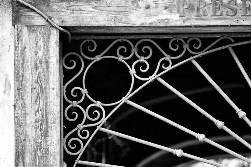 Black and white architectural detail photograph ironwork over the entrance to Preservation Hall, in the French Quarter of New Orleans.