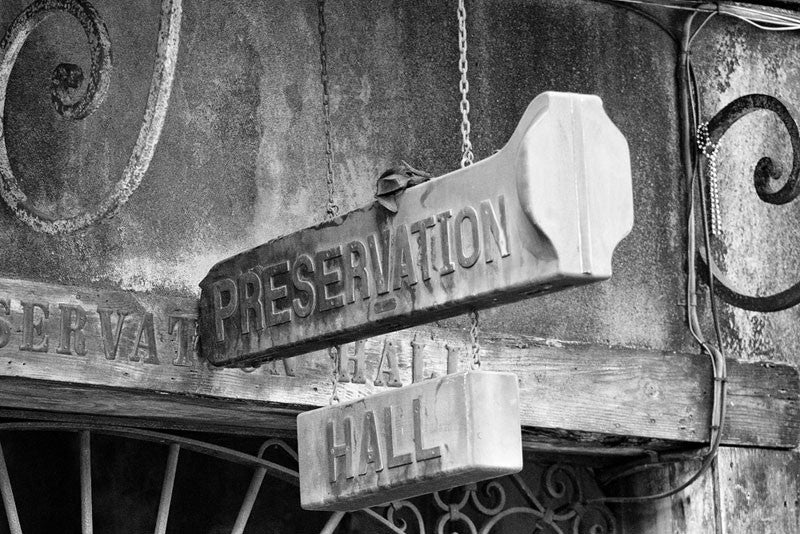 Black and white fine art photograph of the old trombone case sign that hangs over the entrance to the world-famous Preservation Hall in New Orleans' French Quarter.
