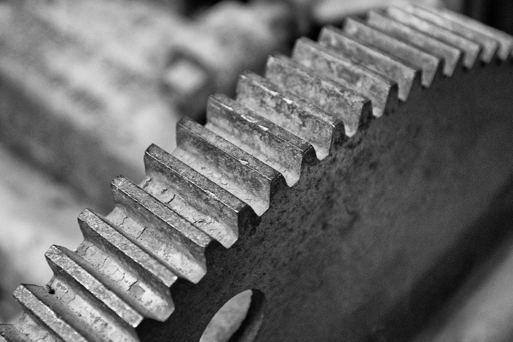 Black and white photograph of a sturdy gear wheel from an antique printing press, focused on the curving row of teeth.