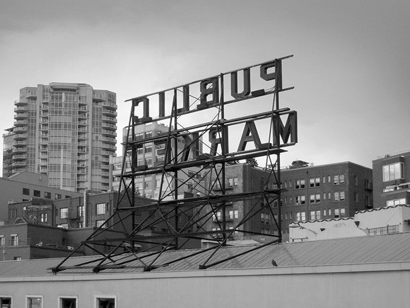 Black and white photograph the skyline of Seattle with the famous Public Market sign seen in reverse. This photograph was sold in Urban Outfitters stores and online as part of their Wall Art Canvas selection.