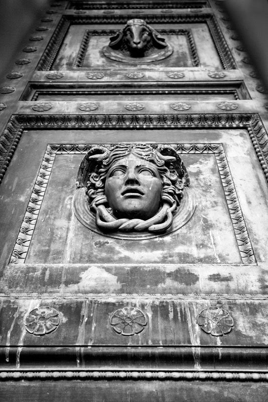 A black and white photograph looking up at one of the huge bronze doors on Nashville's Parthenon.