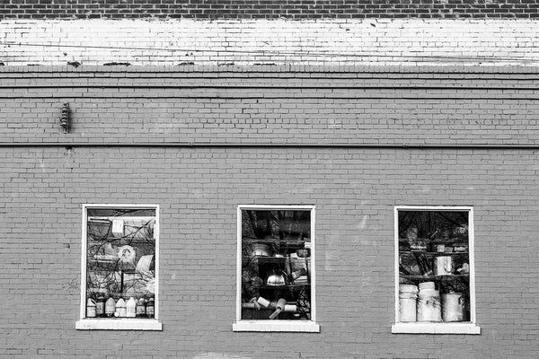 Black and white photograph of three restaurant kitchen windows filled with large cooking pots and other restaurant supplies, seen in East Nashville, Tennessee.
