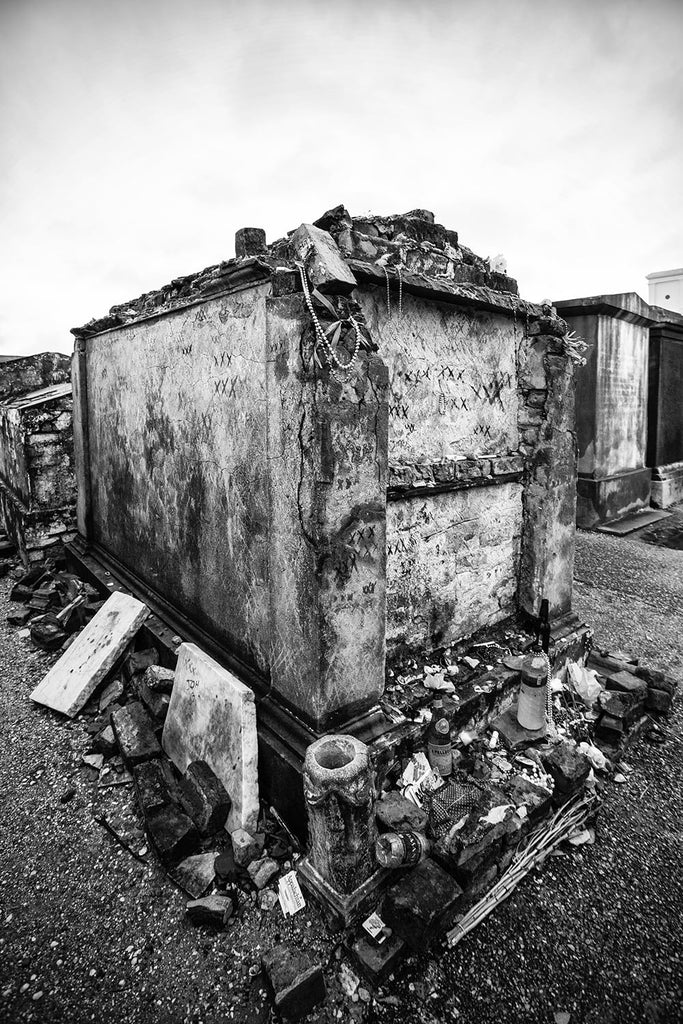 Black and white fine art photograph of a voodoo tomb in New Orleans' famous St. Louis Cemetery No. 1. The old tomb is marked by characteristic triple Xs and littered with offerings around its base.