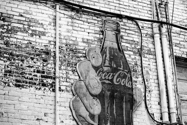 Black and white photograph of a vintage Coca Cola sign featuring a large hand holding a bottle of Coke in a grimy alley in downtown Nashville, Tennessee.