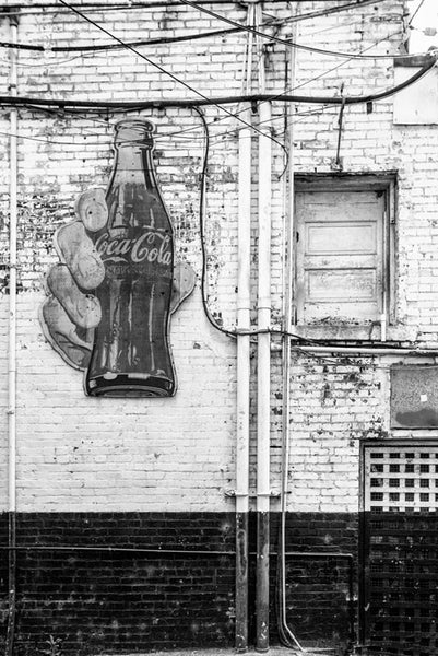 Black and white photograph of a vintage Coca Cola sign in a grimy alley in downtown Nashville, Tennessee.