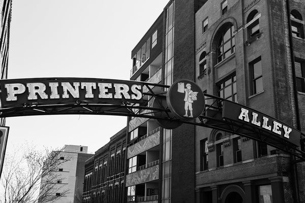 Black and white photograph of the sign that marks the entrance to the famous Printer's Alley entertainment district in Nashville, Tennessee. Originally part of the notorious Nashville men's district of bars and bordellos, the alley transformed into a printing district, with 13 publishers and 10 printers. Nightclubs began entering the area in the 1940s, and the alley remains an entertainment center, even as it again transforms with the entry of modern boutique hotels.