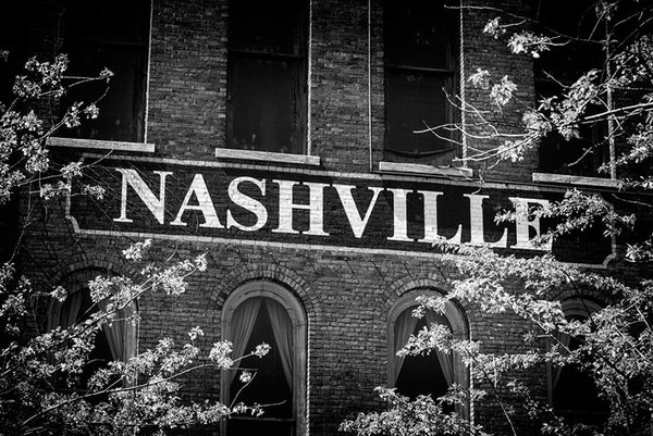 Black and white photograph of a Nashville sign painted on a brick wall facing the Nashville waterfront.