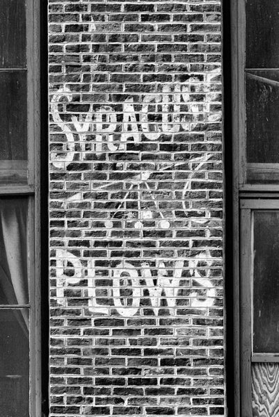Black and white photograph of a vintage hand-painted advertisement for Syracuse Plows, found on a brick wall near the waterfront in downtown Nashville, Tennessee.