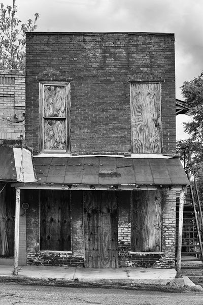 Black and white photograph of an abandoned brick storefront in the deserted downtown of Adams, Tennessee. Adams is famous as the home of the Bell witch legend.