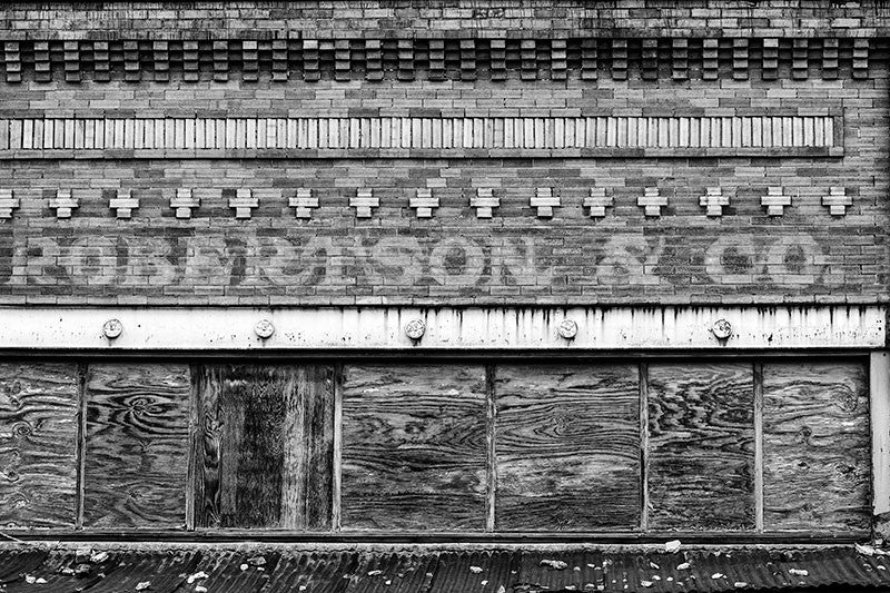 Black and white photograph of the abandoned Robertson & Co. building in the deserted former downtown of Adams, Tennessee. This photograph shows the name of the business in fading white paint on the bricks of the storefront.