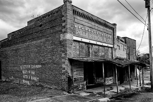 "Black and white photograph of the abandoned Robertson & Co. building in the deserted former downtown of Adams, Tennessee. On the side wall of the building, someone spray-painted  a quote from Jack Kerouac, ""In Autumn Geronimo Weeps — No Pony with a Blanket."""