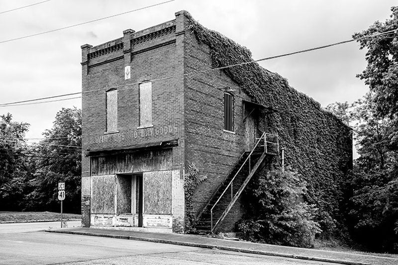Black and white photograph of the abandoned J.E. Winters Co. Dry Goods building, covered with ivy in the old, deserted downtown of Adams, Tennessee. Adams is famous as the home of the Bell witch legend.