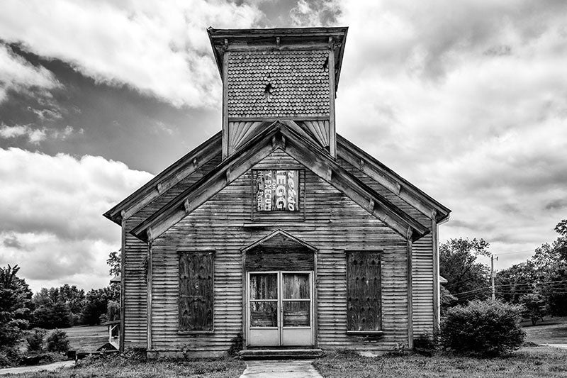 Black and white photograph of an abandoned and boarded-up church in the deserted former downtown of Adams, Tennessee. On the day this photograph was made, a mockingbird in the steeple was loudly protesting my presence.