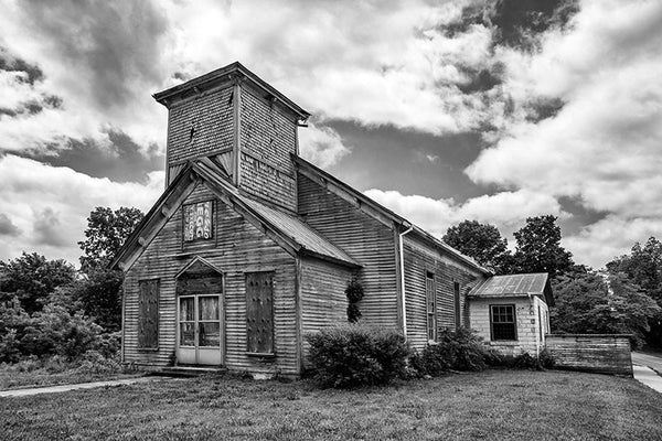 Black and white photograph of an abandoned and boarded-up church in the deserted downtown of Adams, Tennessee. On the day this photograph was made, a mockingbird in the steeple was loudly protesting my presence.
