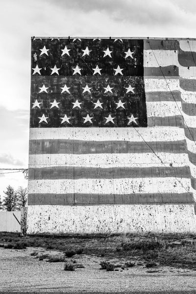 Black and white fine art photograph of a huge, hand-painted US flag on the outside of the Midway Drive-in Theater in the Texas Panhandle.