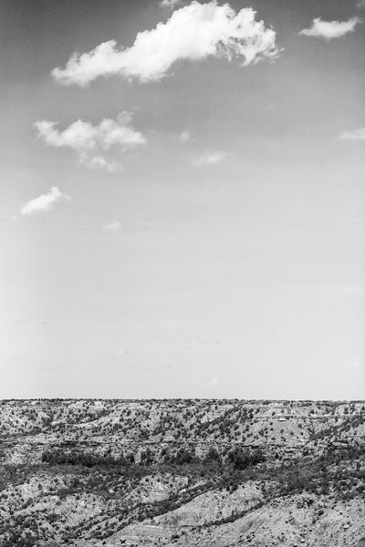 Black and white photograph of the big sky over the rugged landscape of Palo Duro Canyon, in the Texas Panhandle.
