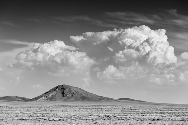 Black and white landscape photograph of the beautiful New Mexico desert featuring a mountain beneath a dramatic bank of late afternoon clouds.