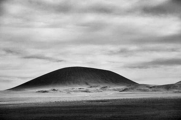 Black and white landscape photograph of an ancient, rounded volcano looming black on the horizon as the daylight goes low on New Mexico, truly the land of enchantment.