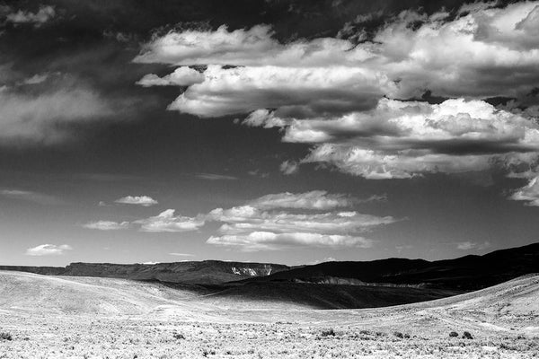 Black and white landscape photograph of Colorado foothills with cloud shadows.