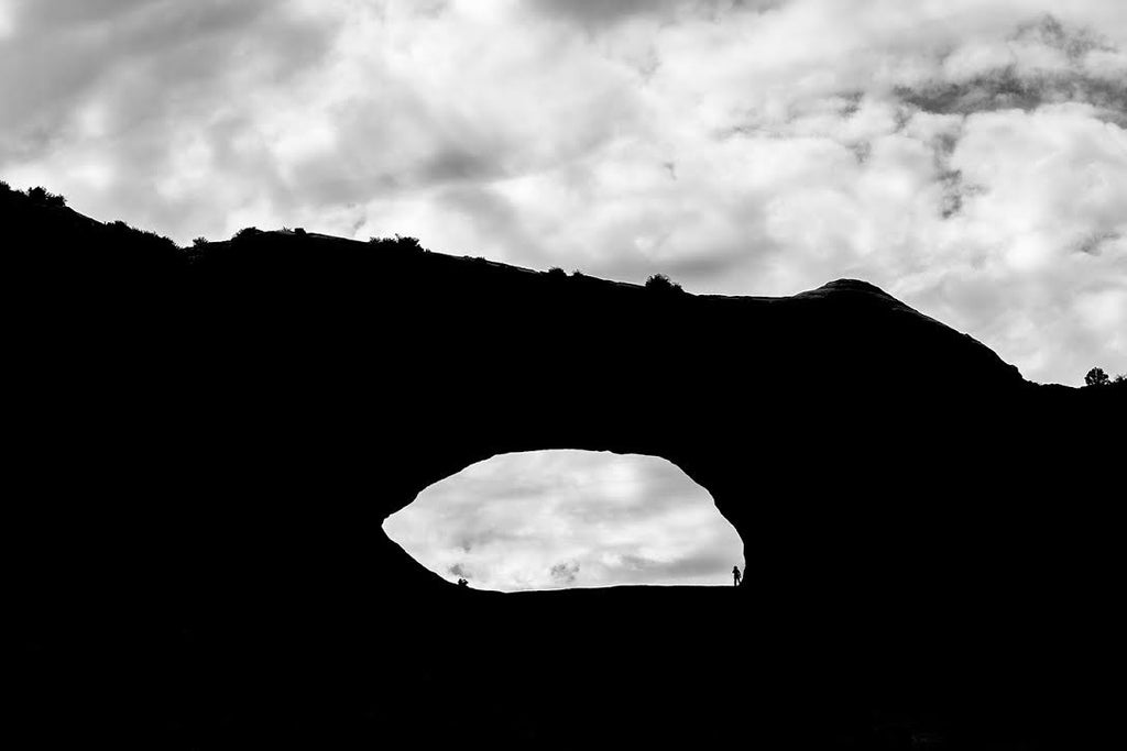Black and white landscape photograph of one of the many arches to be found in the desert landscape of Utah. In this silhouette, two small figures can be seen inside the eye of the arch.