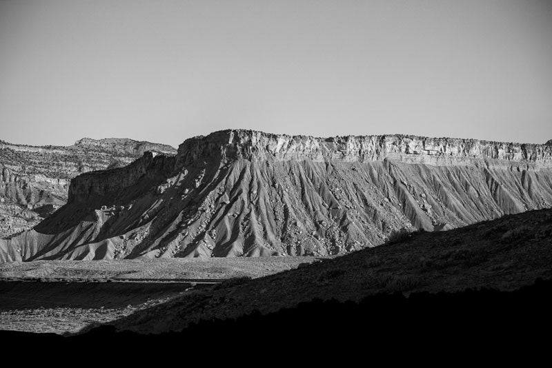 Black and white landscape photograph of a mesa in the Utah desert, captured in the long shadows of early morning.
